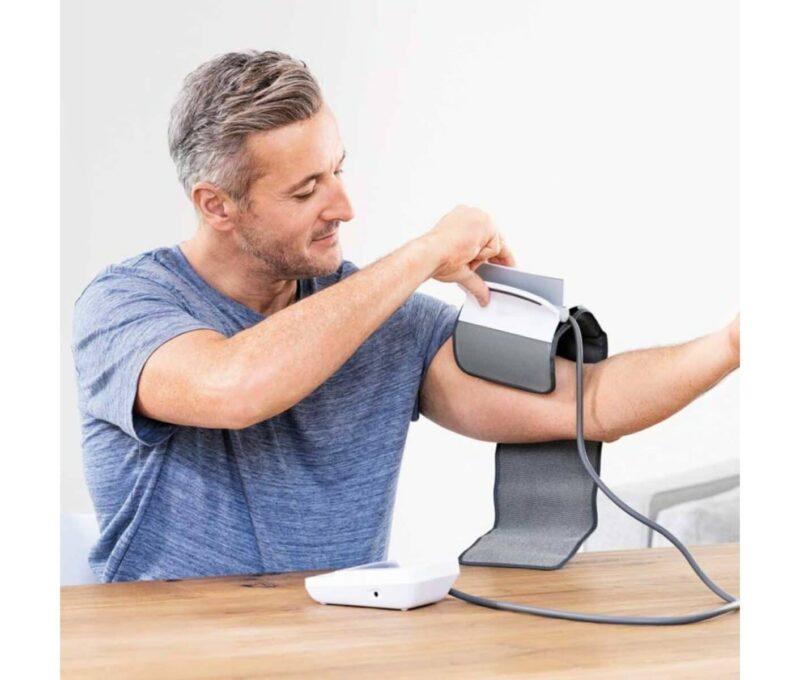 Bilden visar en man som sätter på sig easyClip manschett